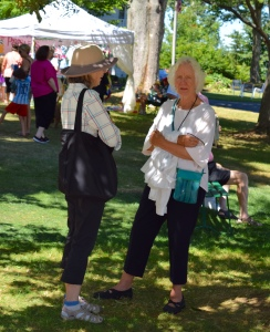 Ladies are finished shopping and talking is always good in the shade on a sunny and 80 day.